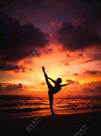 黄昏下海边做瑜伽的女人图片
